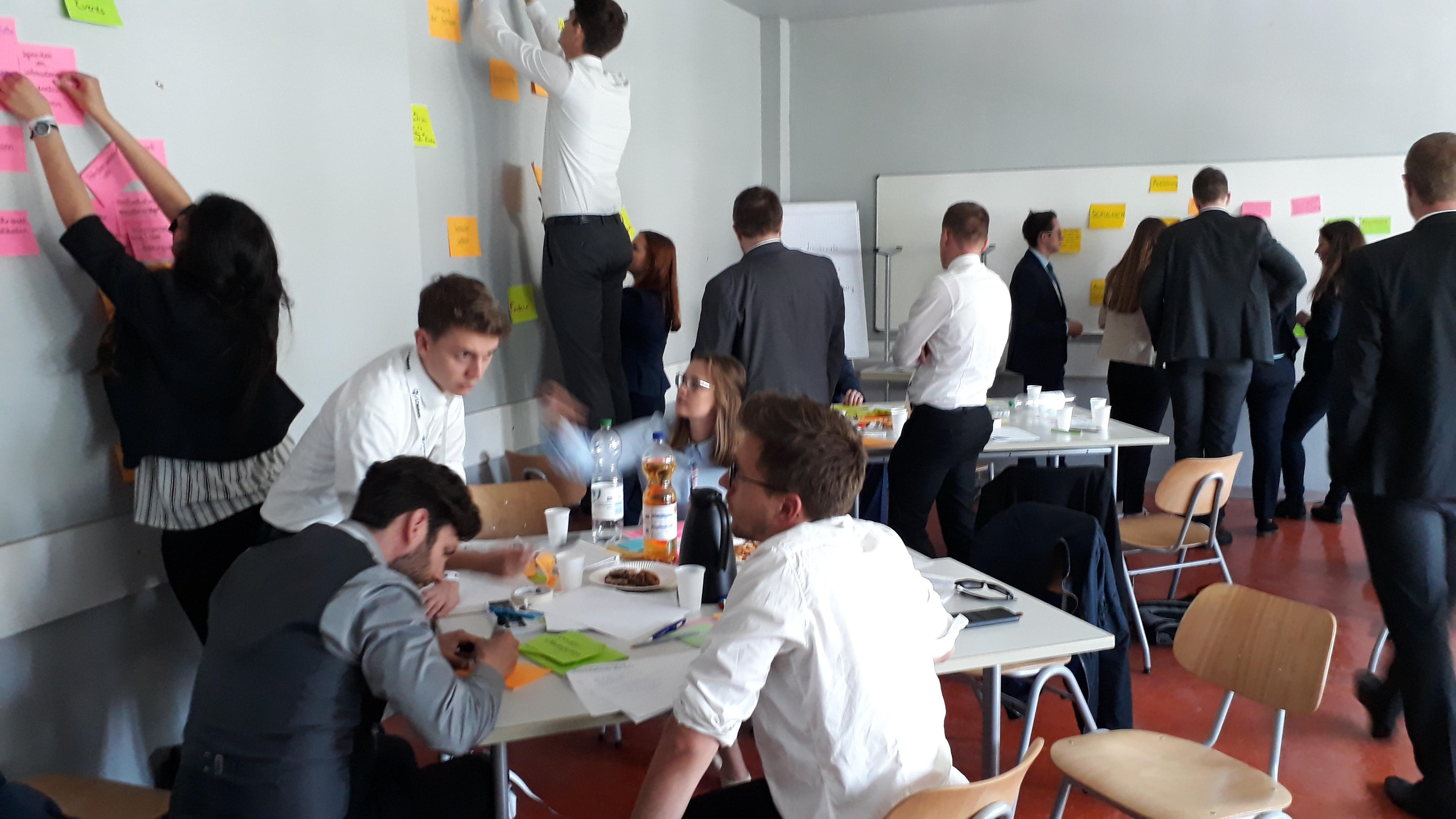 Bild von jungen Teilnehmern, die im Gespräch zusammensitzen und  Post-its mit Ideen an die Wände kleben