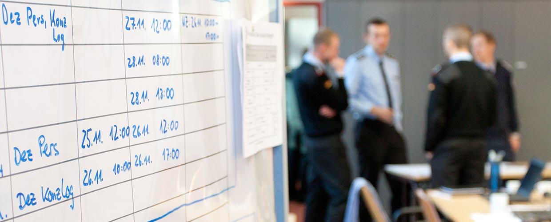 Im Vordergrund ist ein Terminplan an eine Tafel geschrieben, im Hintergrund sieht man Soldaten