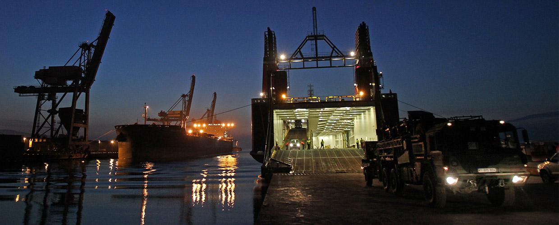 Hafenanlage am Abend; Bundeswehr-LKW verlassen eine Fähre