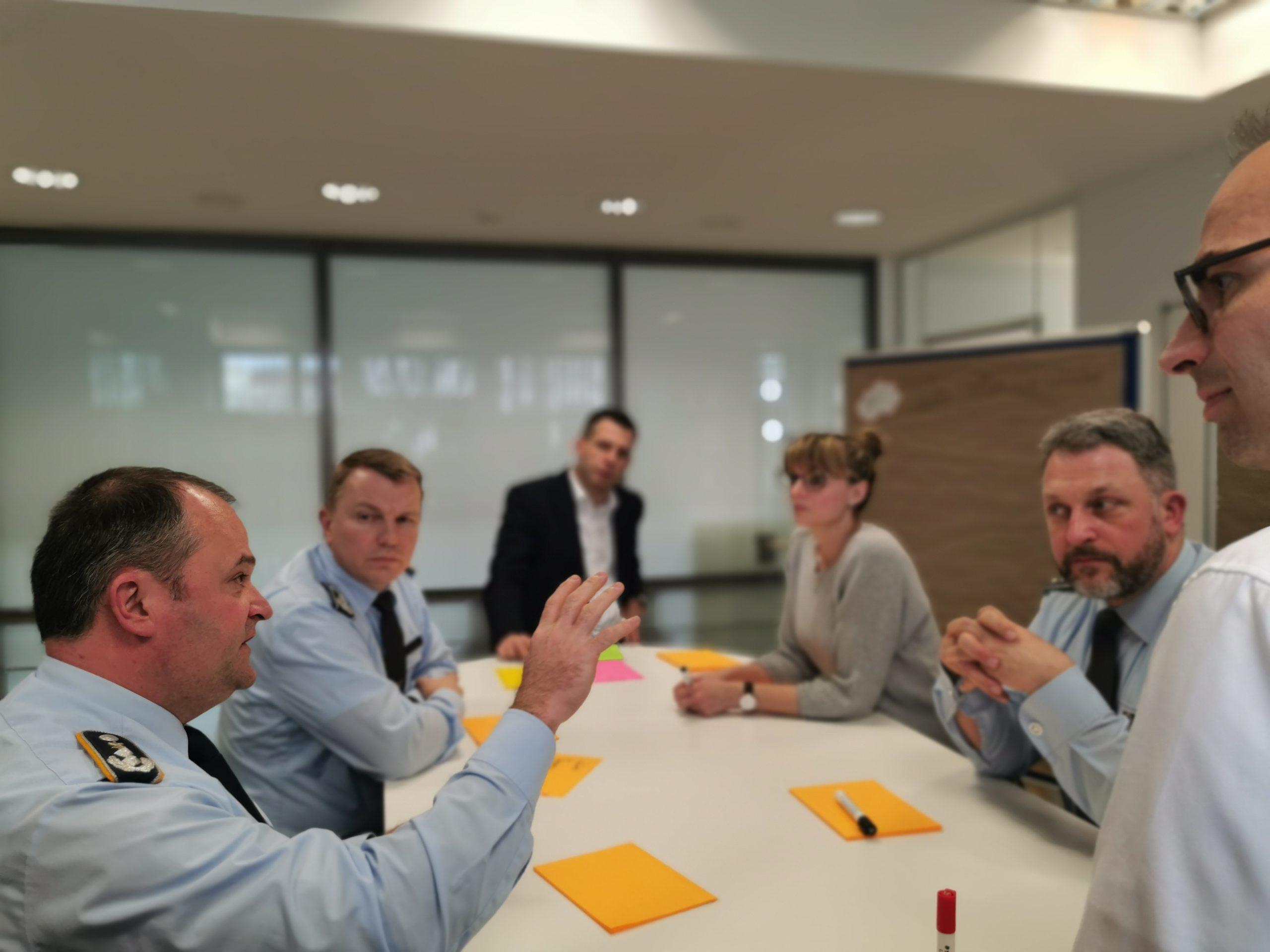 Sechs Personen sitzen diskutierend um einen Besprechungstisch