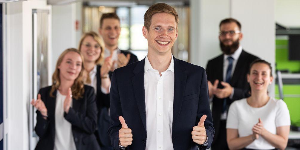 Gruppenbild: Junger Mann in Vordergrund zeigt Daumen hoch