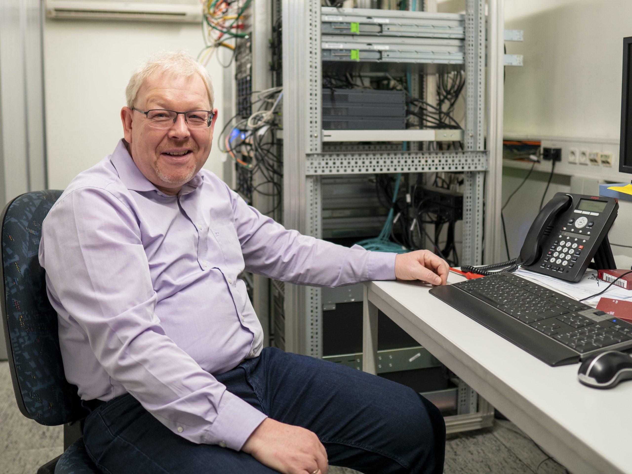Jörg Kraus sitzt im Serverraum des Unternehmens